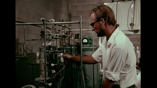 Male scientist in University of Pennsylvania laboratory working w/ potassiumargon radiometric dating equipment MS Researcher spraying rock wall w/...
