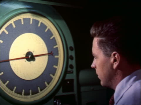 1956 rear view male scientist looking at large dial with red + black needles - scientific experiment stock videos & royalty-free footage