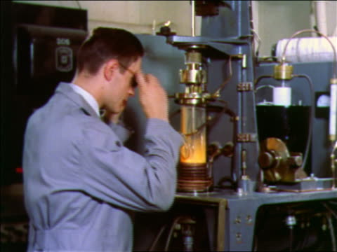 1957 male scientist putting on safety glasses + looking at experiment / bell labs - safety glasses stock videos & royalty-free footage