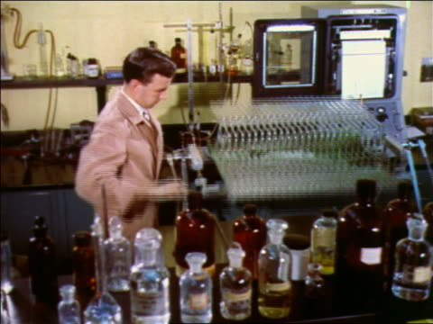 1957 male scientist rocking rack of glass tubes filled with green liquid - 1957 stock videos & royalty-free footage
