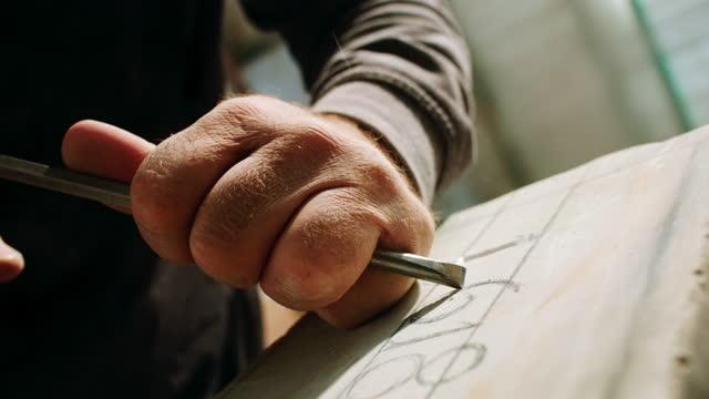slo mo ld scultore maschile che cesella i numeri in pietra - sculpture video stock e b–roll