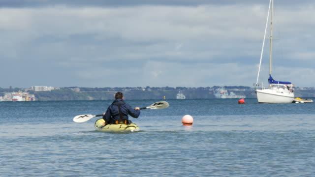 vídeos y material grabado en eventos de stock de male sea kayaker with boats in background - studland heath