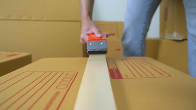 male sealing big box with tape for moving - packaging stock videos & royalty-free footage