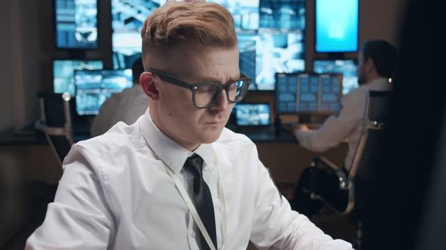 vídeos de stock, filmes e b-roll de um segurança masculino em um escritório com um monte de monitores com leituras de câmeras de vigilância - vestuário de trabalho formal