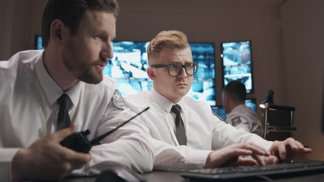 a male security guard in an office with a lot of monitors with readings from surveillance cameras - security screen stock videos & royalty-free footage
