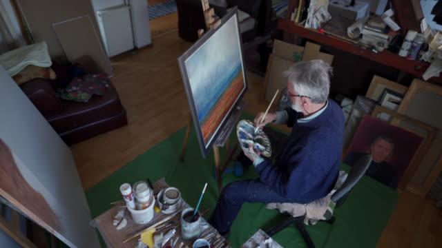 vídeos de stock, filmes e b-roll de retrato sênior masculino da pintura do artista com cores de óleo - painter artist