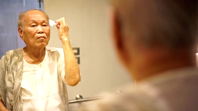 male senior combing his hair at the mirror - vanity stock videos & royalty-free footage