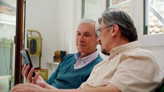 vídeos de stock, filmes e b-roll de amigos seniores do sexo masculino usando celular - amizade masculina