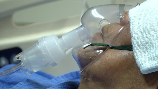 cu  male senior patient breathing via medical ventilator - bed stock videos & royalty-free footage