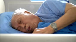 Male senior patient coughing on hospital bed