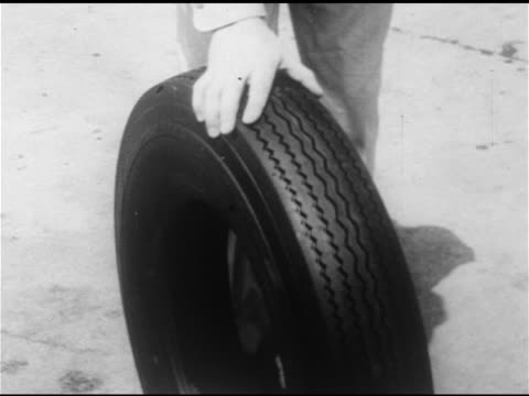 male service station attendant in gulf uniform rolling tire off display rack td ms tire being held by male hand cu gulf tire tread male finger... - filling station attendant stock videos & royalty-free footage