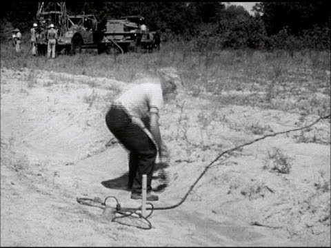 Male setting out seismometer equipment for seismographic survey men setting connected rods into drilled shot hole surrounded by mud water