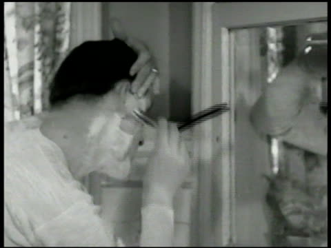 Male shaving face in bathroom mirror Male shaving face w/ straight razor DRAMATIZATION Male touching up gray temples w/ tiny shoeshine brush dipping...