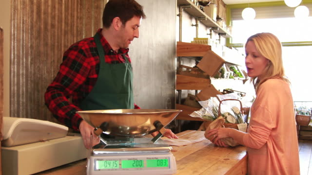 male shop assistant serving customer - scales stock videos & royalty-free footage