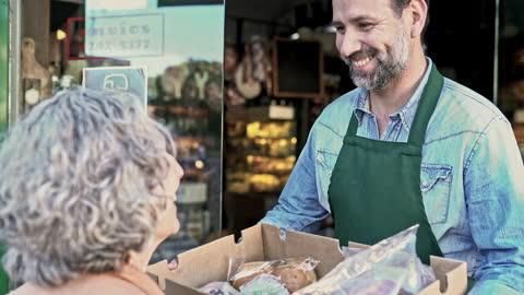 stockvideo's en b-roll-footage met mannelijke winkelier die doos van kruidenierswaren geeft aan hogere klant - klanten georiënteerd