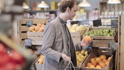 vidéos et rushes de male shopper buying fruit in a grocery store - sentir