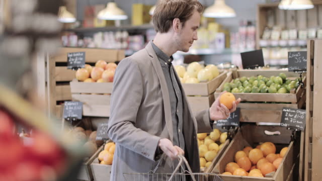 vidéos et rushes de male shopper buying fruit in a grocery store - marché établissement commercial