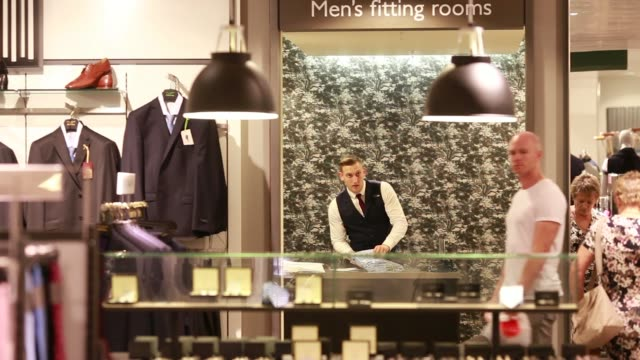 a male shopper looks at clothes hanging on a rack in the mens fashion section in a john lewis plc department store in milton keynes ukon monday july... - part of stock videos & royalty-free footage