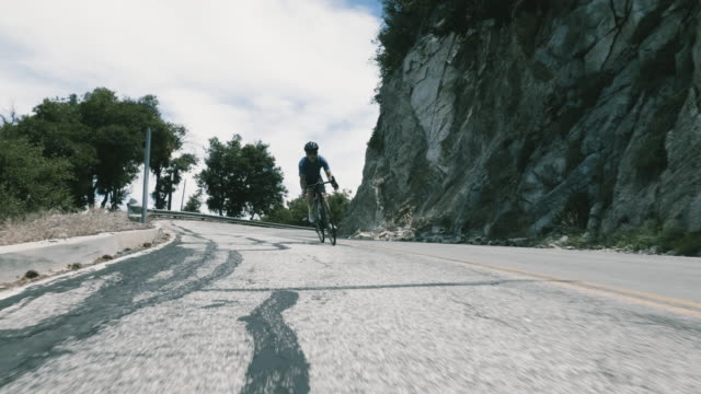 vidéos et rushes de male single senior cyclist descends mountain road, pedaling and riding through corners at high speed - se déplacer vers le bas