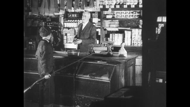 stockvideo's en b-roll-footage met male sitting in rocking chair looking through catalog turning pages w/ rifles young boy buying box of shells in hardware store hunters on lake in... - schommelen schommelstoel