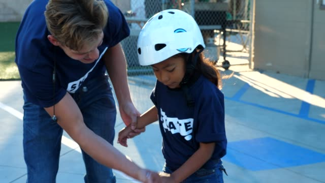 ts male skateboard instructor helping young female student learn to balance on board during summer camp - sports helmet stock videos & royalty-free footage