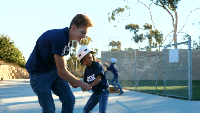 ts male skateboard instructor helping young female student learn to skate during summer camp - a helping hand stock videos & royalty-free footage