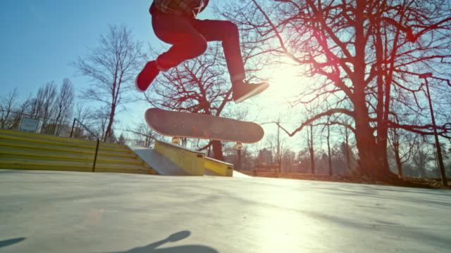 vídeos de stock, filmes e b-roll de slo mo skatista masculino não consegue dar um salto em seu skate no parque urbano de skate em um dia ensolarado - fracasso