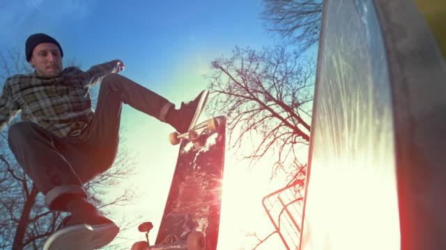 vidéos et rushes de slo mo skateboarder mâle renversant la planche sur la mini-rampe dans le skate park ensoleillé - stunt