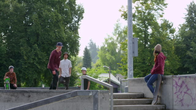 MS Male skateboarder grinding down rail in neighborhood skate park with friends watching in background