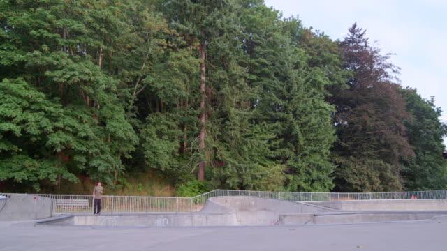 vídeos y material grabado en eventos de stock de ms slo mo male skateboarder performing a trick in mid air in neighborhood skate park - un solo adolescente