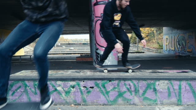 ms male skateboarders skateboarding at urban skate park with graffiti - two people stock videos & royalty-free footage