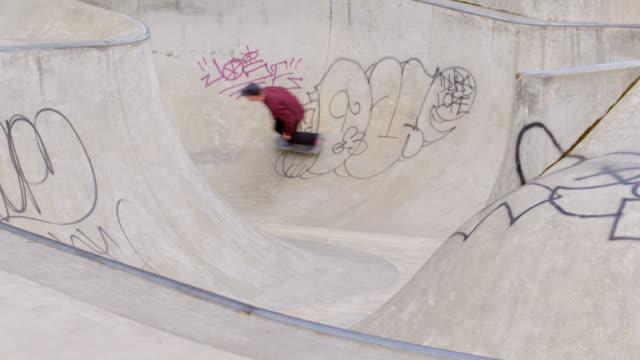 ms male skater skating in bowl of neighborhood skate park - un ragazzo adolescente video stock e b–roll