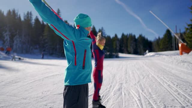 male ski instructor explaining to his client how to use ski pole for exercise at the ski slope - ski pole stock videos & royalty-free footage