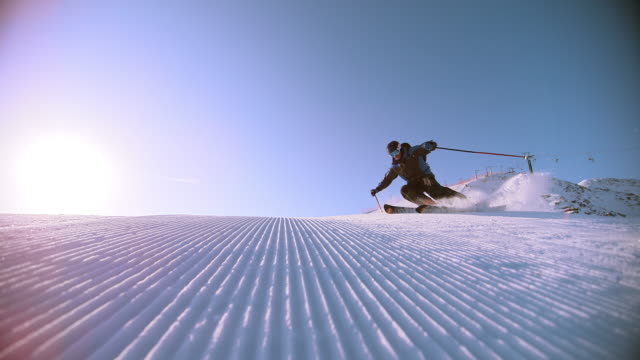 slo mo male skier carving down the ski slope - pulverschnee stock-videos und b-roll-filmmaterial