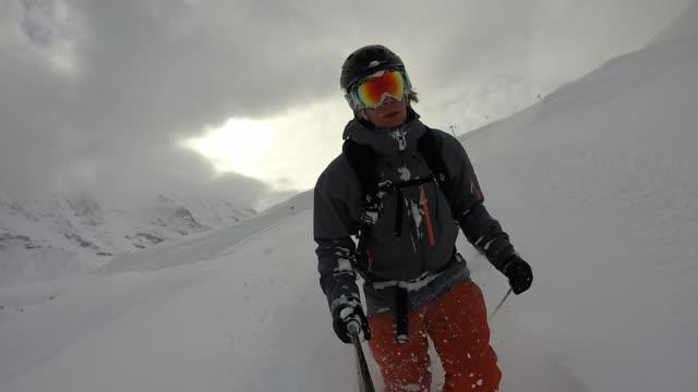 pov dello sciatore maschio che scende pista da neve in polvere - bastoncino da sci video stock e b–roll