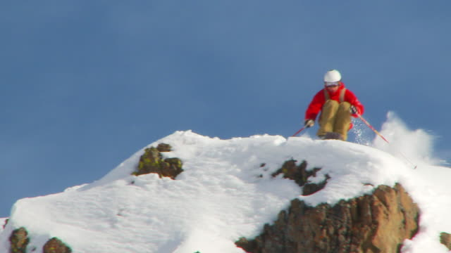 SLO MO male skier drops off fifteen foot rock into powder / Blaine County, Idaho, United States