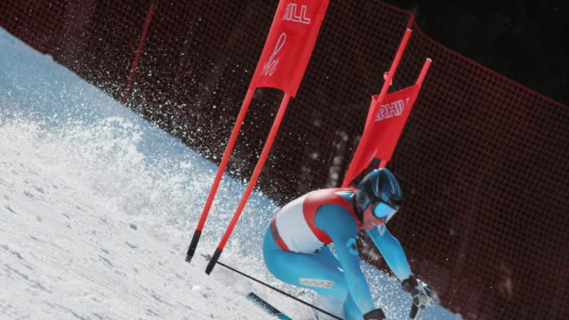SLO MO PAN Male skier in a giant slalom race passing the gate