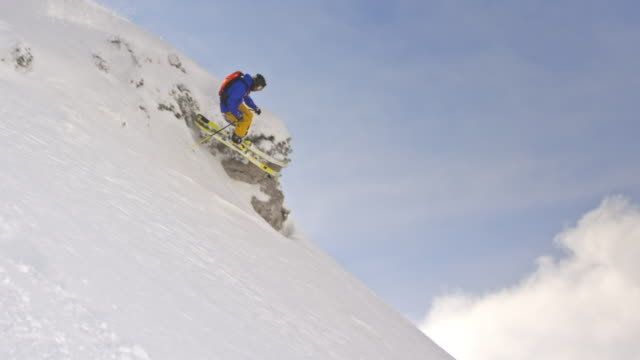 vídeos de stock e filmes b-roll de slo mo male skier skiing down the mountain slope in powder snow - casaco de esqui