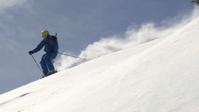 WS TD SLO MO Male skier skiing on ridge / Alta, Snowbird, Utah, USA