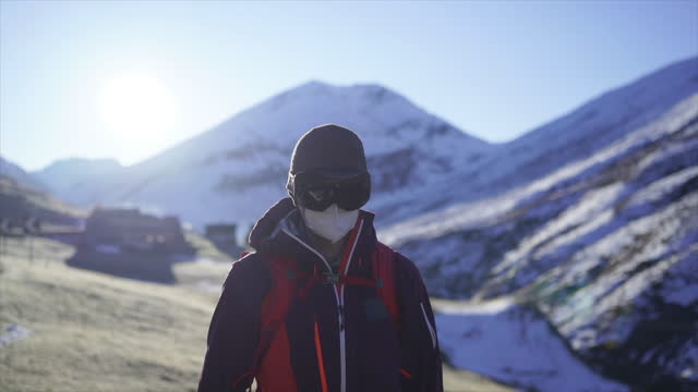 male skier wearing a health mask in the mountains putting on ski goggles - ski goggles stock videos & royalty-free footage