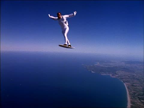 Male skysurfer tumbling over ocean