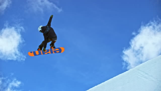 slo mo male snowboarder grabbing his snowboard while jumping into the air in the half-pipe - half pipe stock videos & royalty-free footage