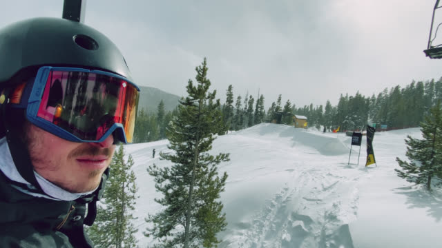 a male snowboarder in his twenties rides a ski lift at eldora ski resort near boulder, colorado on a bright, sunny day - ski holiday stock videos & royalty-free footage