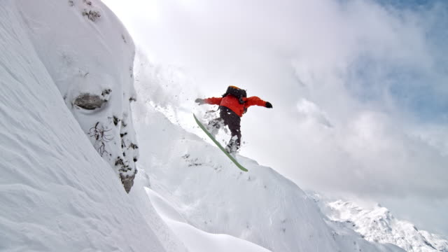slo mo male snowboarder jumping into deep powder - ski stock videos & royalty-free footage