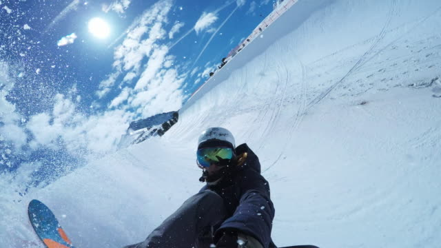 pov male snowboarder riding the half-pipe in sunshine - snowboard video stock e b–roll