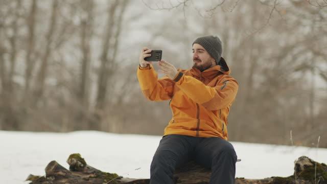 vidéos et rushes de un snowboarder mâle assis sur le coffre de trois prend des photos sur le téléphone d'un beau paysage de station pour les réseaux sociaux. resort blogger stock vidéo - filmer