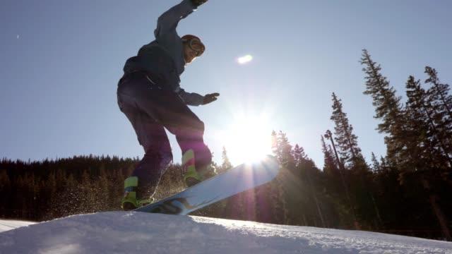 stockvideo's en b-roll-footage met mannelijke snowboarder snowboards op een mooie zonnige dag - sunny