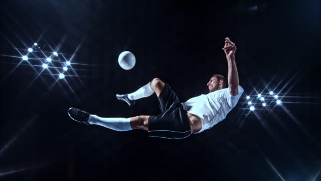 SLO MO LD Male soccer player in white jersey kicking the ball with a scissor kick on a black background