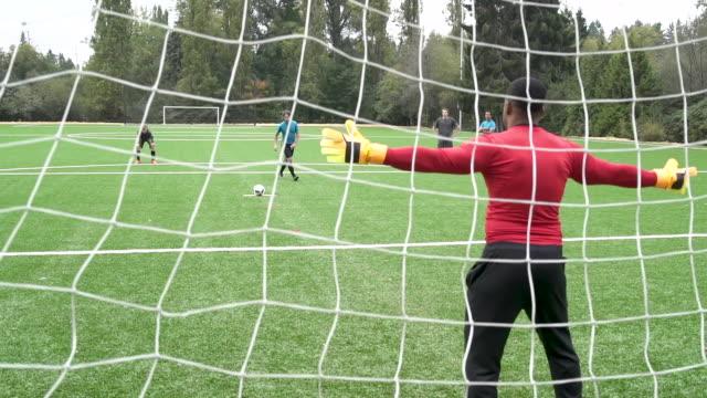 vidéos et rushes de male soccer player scoring goal. - gardien de but