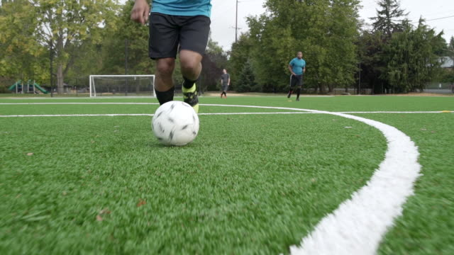 male soccer players playing soccer with lower section of man dribbling ball ahead. - sezione inferiore video stock e b–roll